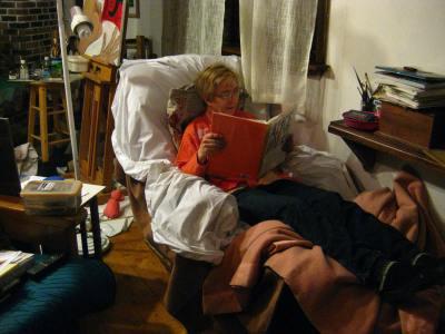 In Recliner, reading about artist, Alice Neel