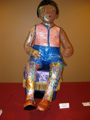 Trudy, papier mache child seated on paper mache hassock