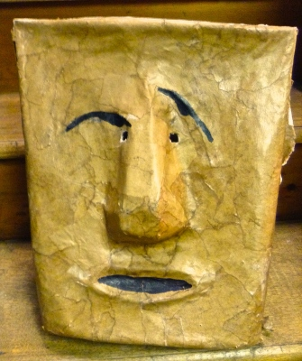 Face Seen on Wastbasket and captured in a mask made of brown paper...